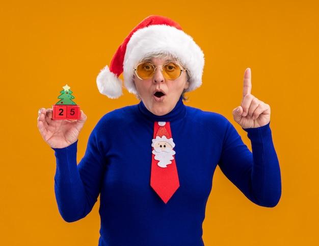 Zaskoczona starsza kobieta w okularach przeciwsłonecznych z czapką mikołaja i krawatem mikołaja trzyma ozdobę choinkową i wskazuje na odizolowaną na pomarańczowej ścianie z miejscem na kopię