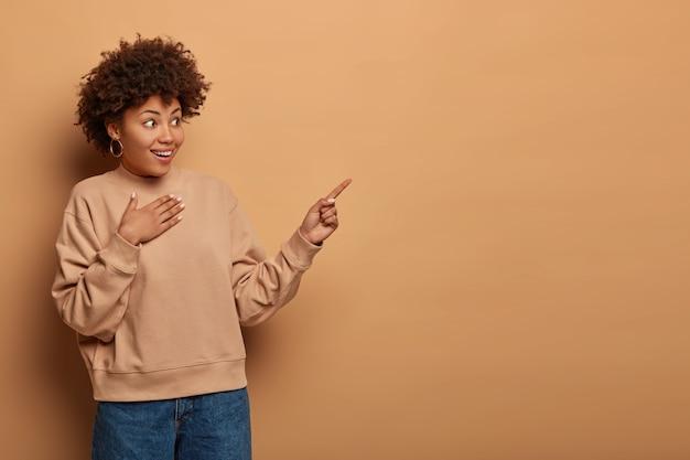 Zaskoczona, szczęśliwa kobieta wskazuje na prawy górny róg z nieoczekiwanym spojrzeniem