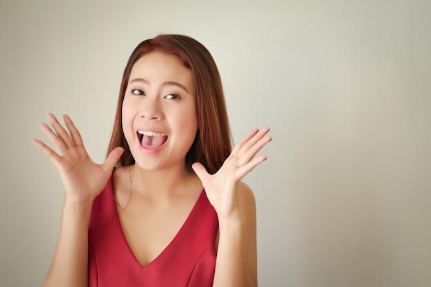 Zaskoczona szczęśliwa uśmiechnięta kobieta pokazująca ekspresję wow