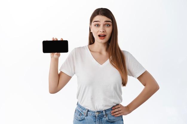 Zaskoczona urocza dziewczyna pokazuje poziomy ekran na smartfonie, zdumiona unosi brwi, udostępnia link, stronę internetową lub aplikację, niesamowitą zawartość online, znalazła coś w internecie, biała ściana