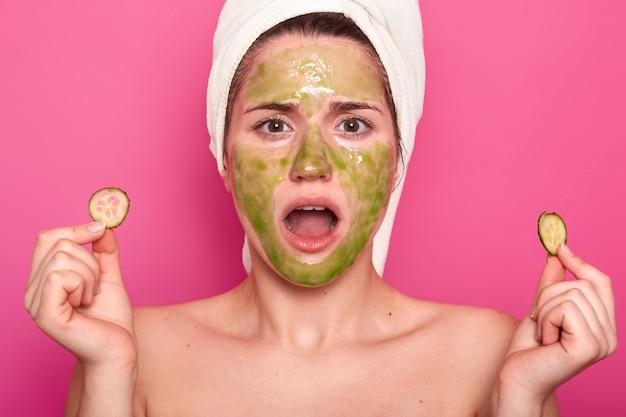 Zaskoczona urocza młoda kobieta trzyma opuszczoną szczękę, patrzy na siebie w lustrze, zszokowana widząc zieloną maskę