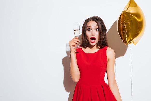 Zaskoczona urocza młoda kobieta z balonem w kształcie gwiazdy i kieliszkiem szampana stojącym na białym tle