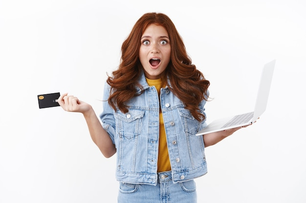 Zaskoczona urocza podekscytowana rudowłosa kobieta w dżinsowej kurtce, wygląda na entuzjastyczną i rozbawioną podczas zakupów online, trzyma laptopa podnosząc kartę kredytową ze zdumienia, dysząc zdumiona fajnymi promocjami internetowymi