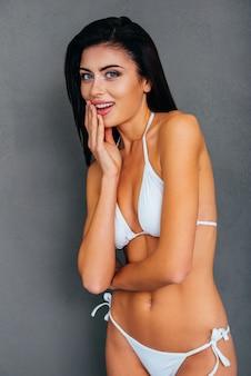 Zaskoczona uroda. zaskoczona młoda kobieta w białym bikini, zakrywająca usta dłonią i patrząca w kamerę, stojąc na szarym tle