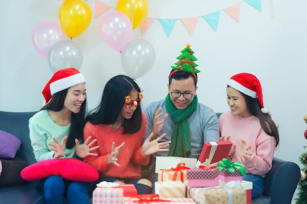 Zaskoczona uśmiechnięta kobieta i przyjaciele z prezentem świątecznym w pudełku otwierającym, wymieniając prezenty świąteczne