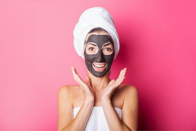Zaskoczona uśmiechnięta młoda kobieta z czarną maską na różowym tle.