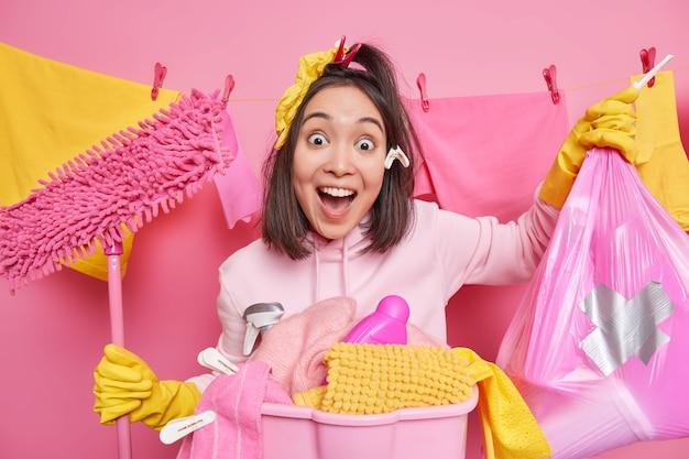 Zaskoczona, wesoła brunetka azjatycka kobieta trzyma usta otwarte, nosi worek na śmieci i pozy mopa w pobliżu kosza na pranie stoi w pobliżu sznura do bielizny przy różowej ścianie