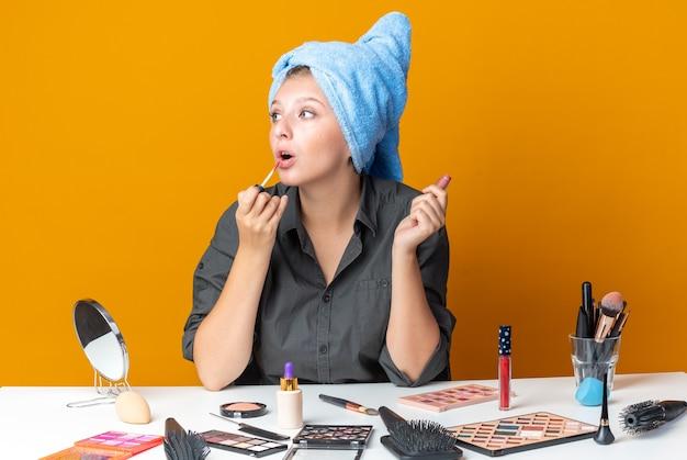 Zaskoczona, wyglądająca strona piękna kobieta siedzi przy stole z narzędziami do makijażu owiniętymi włosami w ręcznik, nakładając błyszczyk