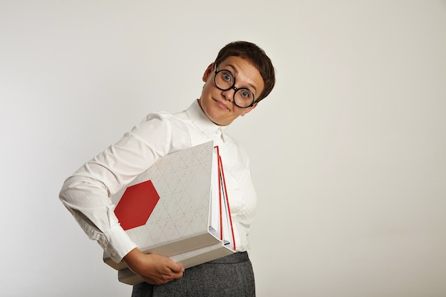 Zaskoczona, zabawna nauczycielka pytająco i trzyma dwa duże foldery z dokumentami z nowym planem edukacyjnym
