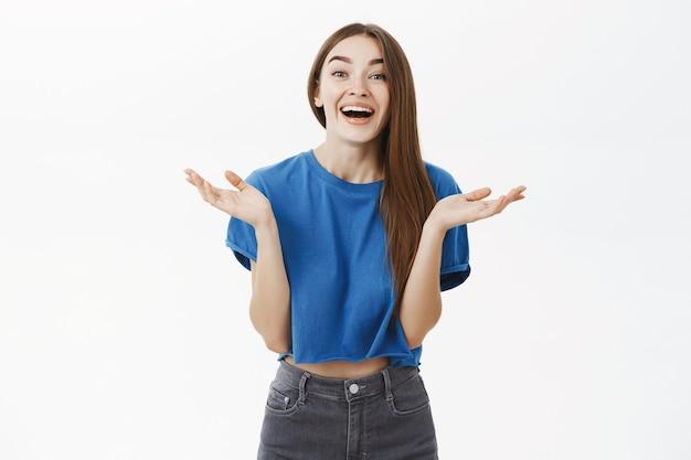 Zaskoczona, zabawna, stylowa, pełna emocji kobieta z długimi brązowymi włosami w niebieskiej, przyciętej koszulce, klaszcząca w dłonie z rozbawienia i szczęścia, uśmiechająca się radośnie i spoglądająca entuzjastycznie przez szarą ścianę