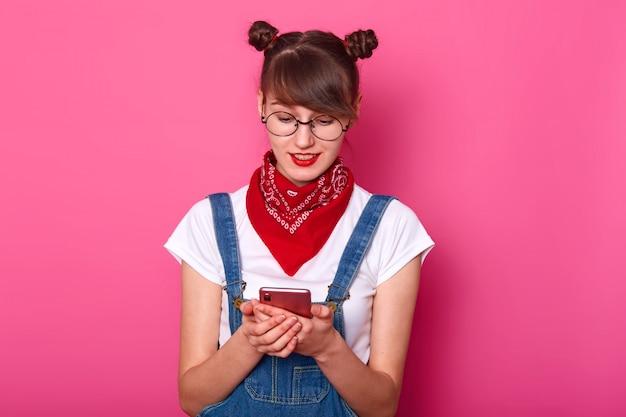 Zaskoczona zadowolona słodka kobieta wpisująca wiadomości na swoim telefonie, oglądająca filmy, ubrana w stylowy kombinezon dżinsowy