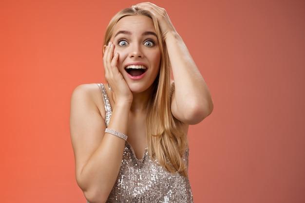 Zaskoczona zadowolona szczęśliwa młoda atrakcyjna kobieta oniemiała zerkając aparatem wytrzeszczone oczy zrobiły wrażenie dotykając głowy krzyczącej zdziwiony zszokowany, zdziwiona stojąca srebrna wieczorowa suknia wieczorowa.