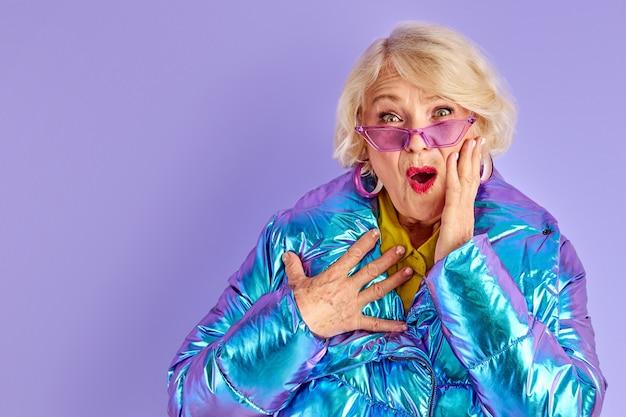Zaskoczona, zaskoczona dama uśmiechnięta, stojąca na wysokości stawu skokowego z szeroko otwartymi ustami, w okularach przeciwsłonecznych, odizolowana na fioletowej przestrzeni