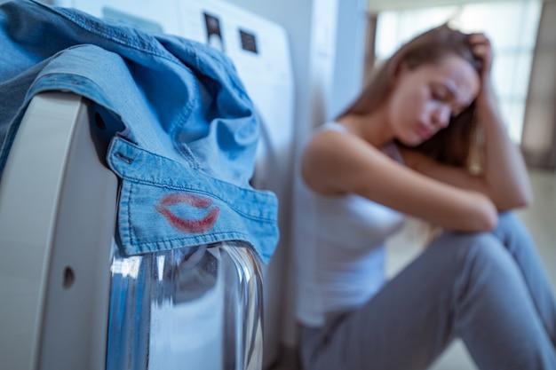 Zaskoczona zdenerwowana zestresowana płacząca kobieta znaleziona na kołnierzu koszuli męża nosi ślady czerwonej szminki podczas prania