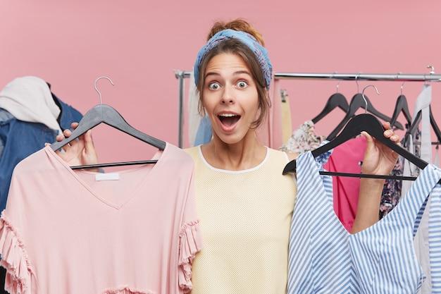 Zaskoczona, zdziwiona ładna kobieta ubrana na co dzień, wybiera sukienkę do codziennej pracy, trzymając w dłoniach dwa wieszaki z ubraniami w szoku, by kupić ją w wyprzedaży. niskie ceny i wyprzedaż