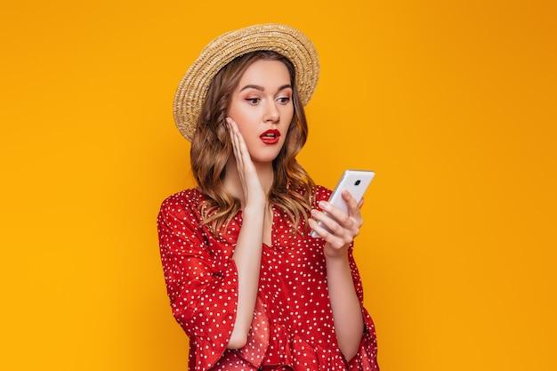 Zaskoczona, zszokowana dziewczyna w czerwonej sukience i słomkowym kapeluszu trzyma telefon komórkowy i patrzy, jak czyta wiadomość sms i robi zakupy online na pomarańczowej ścianie. letnia dziewczyna z komórką