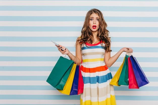 Zaskoczona, zszokowana dziewczyna z torbą na zakupy przestała rozmawiać przez telefon z tego, co zobaczyła ze zniżką. kobiece pełnej długości zdjęcie na niebieskiej ścianie w paski.