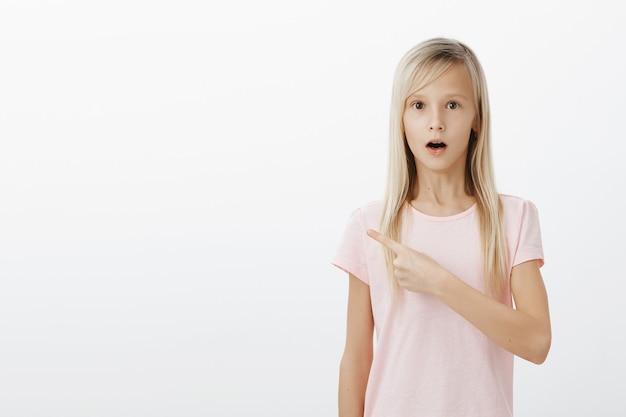Zaskoczona, zszokowana mała dziewczynka wskazując palcem w lewo
