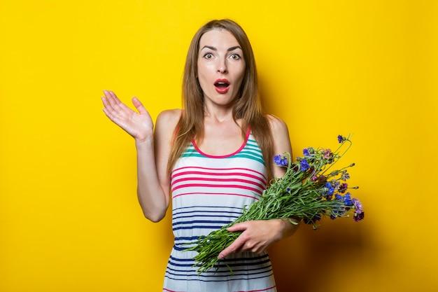 Zaskoczona, zszokowana młoda dziewczyna w pasiastej sukience z polnymi kwiatami