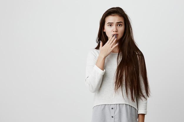 Zaskoczona zszokowana modelka z prostymi ciemnymi włosami, ubrana w swobodne ubrania, patrząca na zepsute oczy i oszołomienie, oszołomiona i przestraszona z powodu wiadomości, które usłyszała.