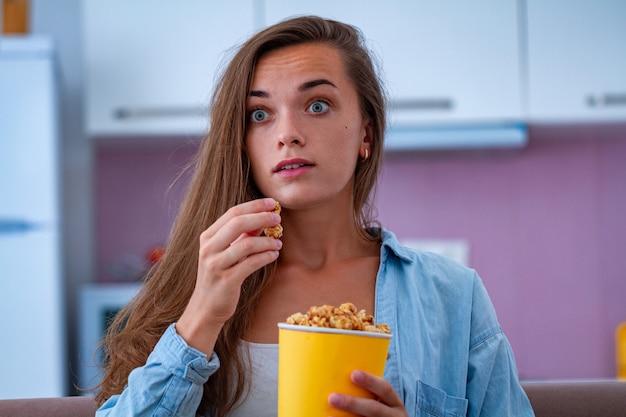Zaskoczona zszokowana niespokojna kobieta jedząca chrupiącego karmelowego popcorn podczas oglądania horroru w domu. film z popcornem