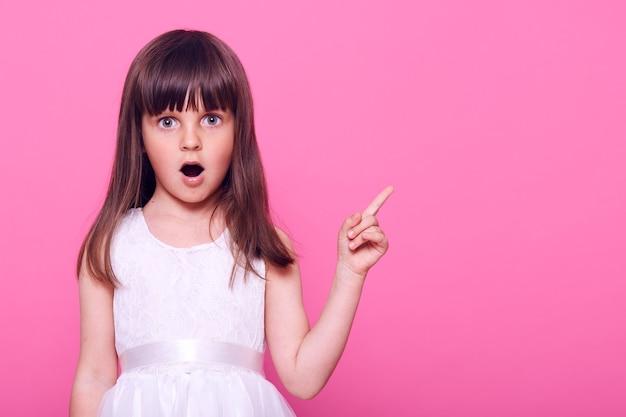 Zaskoczone dziecko płci żeńskiej ubrane w piękną białą sukienkę wskazującą na bok przednim palcem z szeroko otwartymi ustami, widzi coś zdumiewającego, kopiuje przestrzeń, odizolowane na różowej ścianie