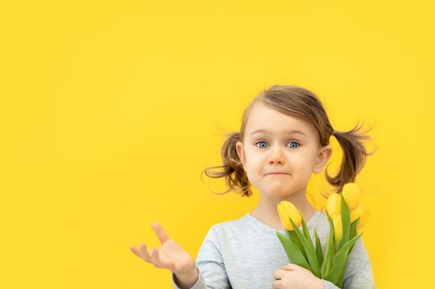 Zaskoczone dziecko trzyma bukiet żółtych tulipanów