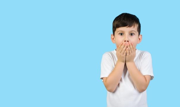 Zaskoczone dziecko w białej koszulce zakrywa usta rękami