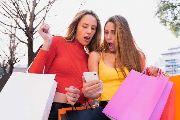 Zaskoczone dziewczyny patrząc na telefon
