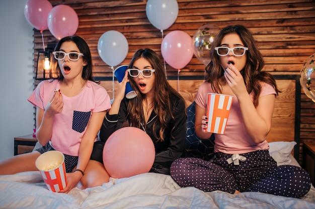 Zaskoczone i podekscytowane młode kobiety siedzą na łóżku w świątecznym pokoju i oglądają ruchy. są to specjalne okulary. dziewczyny są podekscytowane. dwie kobiety trzymają wiadra z popcornem. trzeci ma kubek z colą.