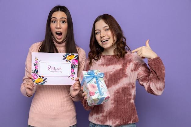 Zaskoczone kobiety w szczęśliwy dzień kobiet trzymające kartkę z życzeniami z prezentem