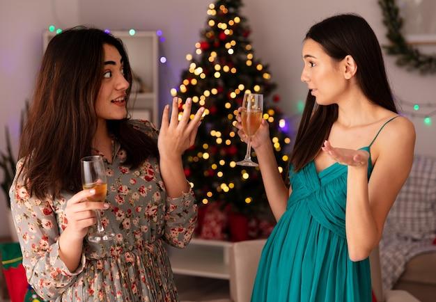 Zaskoczone, ładne młode dziewczyny trzymają kieliszki szampana i patrzą na siebie, ciesząc się świętami w domu