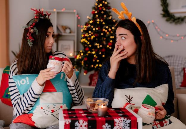 Zaskoczone ładne młode dziewczyny z wieńcem ostrokrzewu i opaską renifera trzymają kubki, patrząc na siebie siedząc na fotelach i ciesząc się świętami w domu