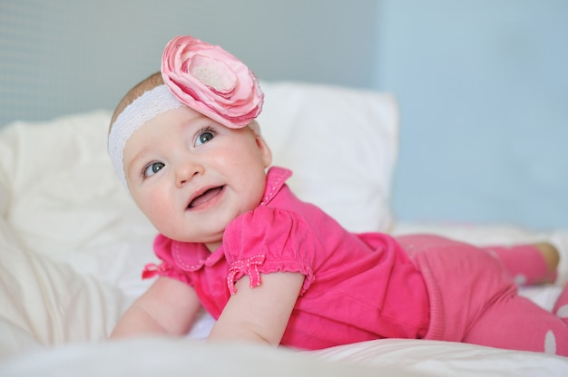 Zaskoczone, słodkie maleństwo z pulchnymi policzkami w różowym ubranku i kwiatuszku