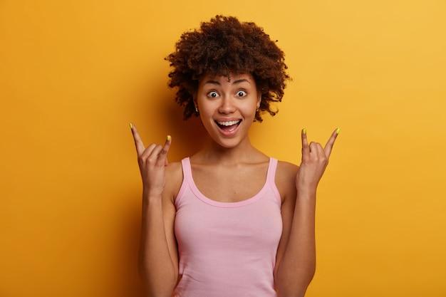 Zaskoczony african american kobieta sprawia, że rock n roll znak ręką