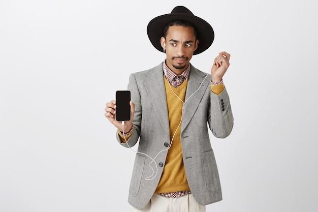 Zaskoczony afroamerykanin zdejmujący słuchawki zdezorientowany i niezręczny, patrząc na ekran smartfona, pokazujący coś dziwnego na wyświetlaczu telefonu komórkowego