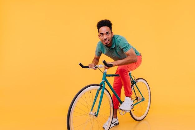 Zaskoczony afrykański facet w czerwonych spodniach, jazda na rowerze. kryty zdjęcie śmieszne czarny młody człowiek siedzi na rowerze.