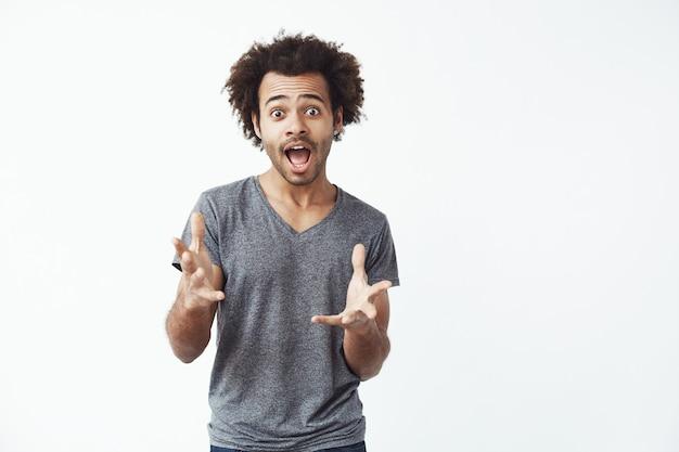 Zaskoczony afrykański mężczyzna z otwartymi ustami gestykulacji.