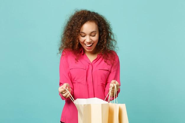 Zaskoczony afryki dziewczyna w różowe ubrania dorywczo trzymać pakiet torba z zakupami po zakupach na białym tle na tle niebieskiej ściany turkus. koncepcja życia szczere emocje ludzi. makieta miejsca na kopię.