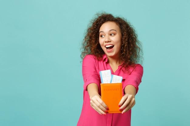 Zaskoczony afryki dziewczyna w różowe ubrania dorywczo trzymając bilet na kartę pokładową paszport na białym tle na tle niebieskiej ściany turkus w studio. koncepcja życia szczere emocje ludzi. makieta miejsca na kopię.