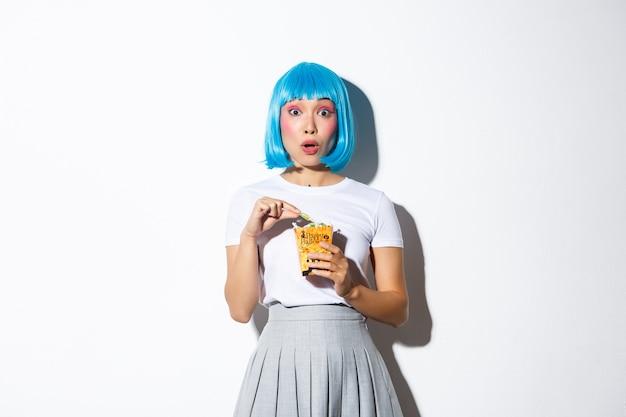 Zaskoczony asian dziewczyna w niebieskiej peruce i kostium na halloween, trzymając torbę z smakołykami, stojąc.