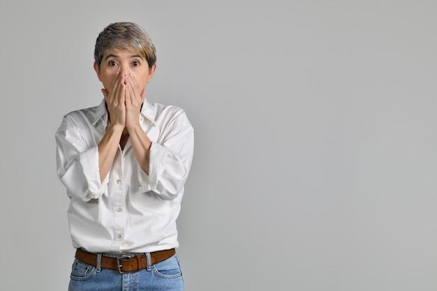 Zaskoczony azji kobieta w średnim wieku krzyczy na białym tle. patrząc w kamerę