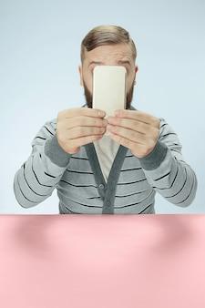 Zaskoczony biznesmen rozmawia przez telefon, siedząc przy stole. pojęcie męskich emocji