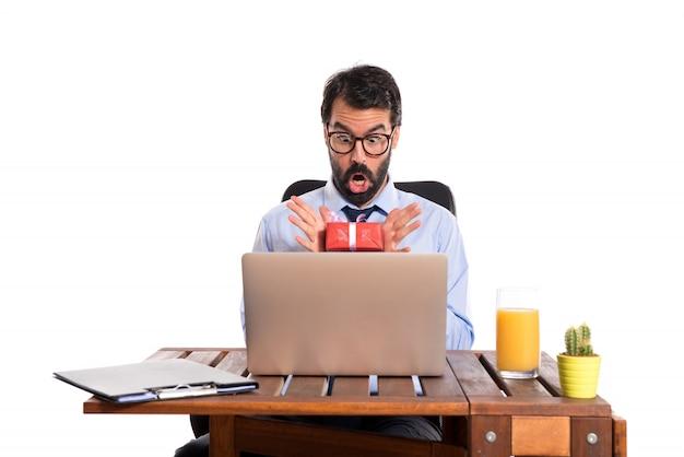 Zaskoczony biznesmen w swoim biurze z prezentem
