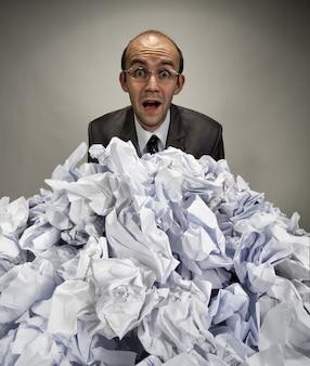Zaskoczony biznesmen wyciąga rękę z pogniecionych papierów