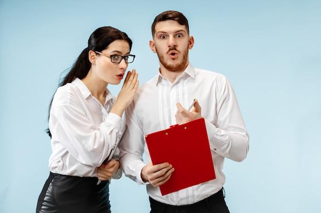 Zaskoczony biznesowy mężczyzna i kobieta uśmiechając się na niebieskim tle studia
