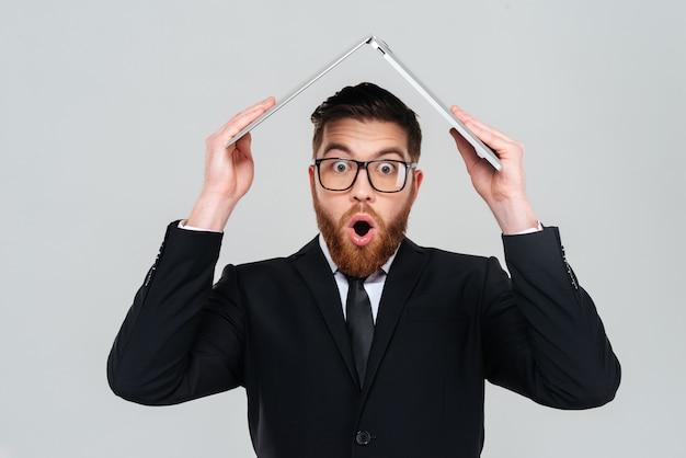 Zaskoczony brodaty biznesmen w okularach i czarnym garniturze, trzymający laptopa nad głową