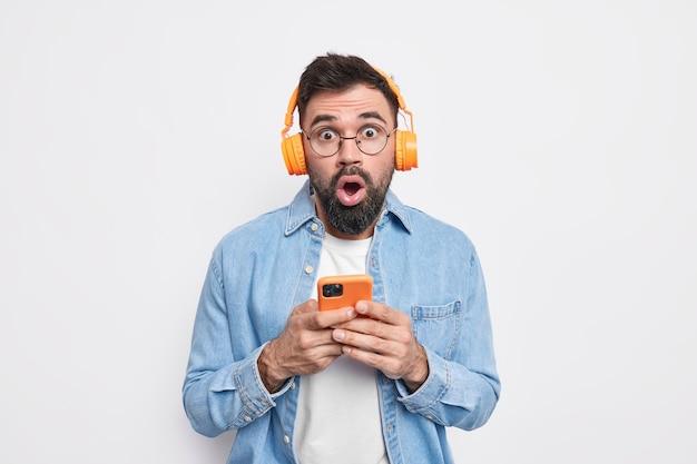 Zaskoczony brodaty mężczyzna jest pod wrażeniem, używa telefonu komórkowego i słuchawek stereo do słuchania muzyki z listy odtwarzania, nosi dżinsową koszulę