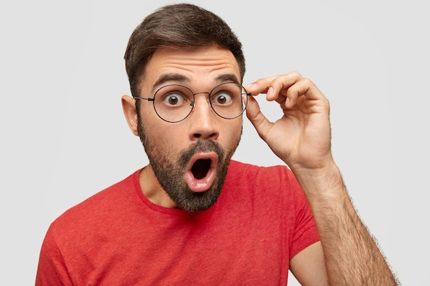 Zaskoczony brodaty mężczyzna nosi czerwoną casualową koszulkę i okulary, otwiera usta, woła ze zdumieniem, zszokowany swoimi obowiązkami w pracy, nie oczekuje takiej odpowiedzialności, odizolowany na białej ścianie