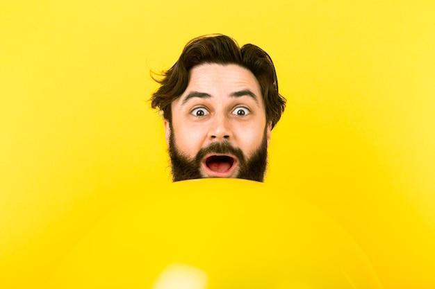 Zaskoczony brodaty mężczyzna patrząc z żółtego balonu, koncepcja pozytywne emocje